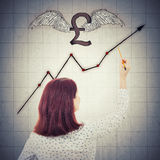 Pound rising graph. Rear view of a young businesswoman, holding a pencil, drawing winged pound sign and a rising graph on gray wall background. Concept of royalty free stock images