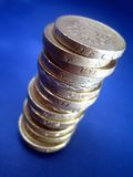 Pound stack. Stack of pound coins over blue, shallow DoF stock photo