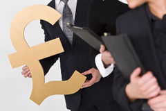Pound Sterling. Concept shot showing business people standing in a line, the last of whom is carrying a large golden British Pound Sterling symbol Stock Photos