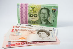 Pound sterling and baht money. Royalty Free Stock Images