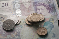 Pound sterling and coins loose money. Pile of loose cash for savings five English pounds sterling and 20 pound note £1 and 50p coins royalty free stock image