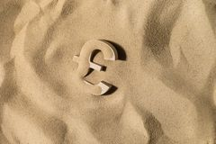 Pound Symbol Under the Sand. British Pound Sterling Symbol or Sign Covered with Sand in the Sun after Crisis royalty free stock photography