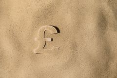 Pound Symbol Under the Sand. British Pound Sterling Symbol or Sign Covered with Sand in the Sun after Crisis stock images