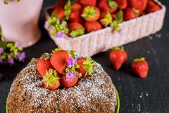 Pound vanilla cake and basket with fresh strawberries. And flowers, biscuit, bundt, homemade, fruit, round, food, dessert, sweet, baked, bakery, sugar, tasty royalty free stock photos