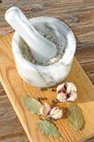 Pounder, quattro spezie, aglio e foglia di alloro su un fondo di legno Immagini Stock Libere da Diritti