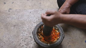 Pounding Thai chili sauce. In stone mortar with pestle stock video footage