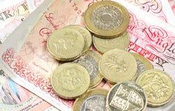 Poundmünzen auf Geldhintergrund Lizenzfreie Stockfotos