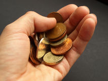 Pounds. Hand with British Pounds coins (UK currency) over a dark background Royalty Free Stock Photo