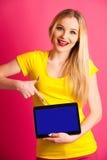 Pounting adolescente rubio hermoso de la mujer en tableta en blanco como adver Fotografía de archivo