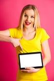 Pounting adolescente rubio hermoso de la mujer en tableta en blanco como adver Imagenes de archivo