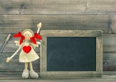 Poupée avec le coeur rouge Décoration de jour de valentines avec le tableau noir Photo stock