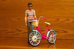 Poupée avec une bicyclette Images stock