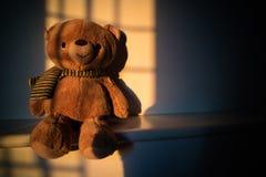 Poupée d'ours de nounours se reposant près de la fenêtre avec la lumière de coucher du soleil cop Images libres de droits