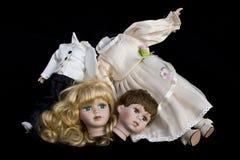 Poupée de fille et de garçon cassée épousant le corps sur le fond noir Photographie stock
