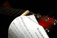 Poupée de guitare avec une musique de feuille de bleus Images stock