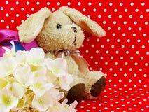 Poupée de lapin avec le boîte-cadeau rose de coeur et la fleur artificielle sur le fond rouge de point de polka Images libres de droits