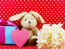 Poupée de lapin avec le boîte-cadeau rose de coeur et la fleur artificielle sur le fond rouge de point de polka Photographie stock