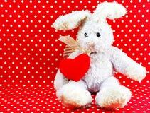 Poupée de lapin avec le coeur rouge sur le fond rouge de point de polka Images libres de droits