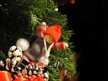 Poupée de Noël heureux avec les cheveux blonds et le chapeau rouge dans les aiguilles Photo libre de droits
