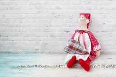 Poupée de Tilda dans un chapeau rouge, et dans une robe rouge avec le quatre-morceau La poupée se repose sur une table légère en  photo stock