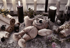 Poupée de vaudou avec les bougies noires et les rouleaux antiques Photographie stock libre de droits