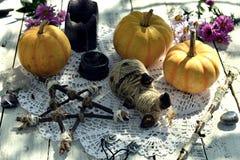 Poupée de vaudou avec les potirons, le pentagone étoilé et les bougies noires sur la serviette de dentelle photographie stock libre de droits