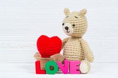 Poupée douce d'ours de nounours avec le texte d'amour et le coeur de tricotage rouge dessus Photos stock