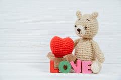 Poupée douce d'ours de nounours avec le texte d'amour et le coeur de tricotage rouge dessus Photographie stock
