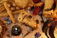 Poupée effrayante de vaudou avec les plumes de coq, la bougie noire, la croix et les rouleaux de papier sur la table de sorcière photographie stock libre de droits