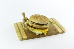 Poupée en bois tenant un hamburger Photos stock
