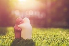 Poupée en céramique blanche et rose sur l'herbe verte avec le bokeh de tache floue et le s Image libre de droits