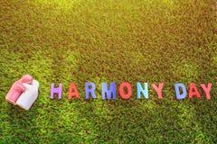 Poupée en céramique blanche et rose sur l'herbe verte avec le texte en bois HARMO Photos libres de droits