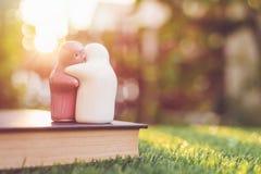 Poupée en céramique blanche et rose sur le livre avec le bokeh et la lumière du soleil de tache floue Photo stock