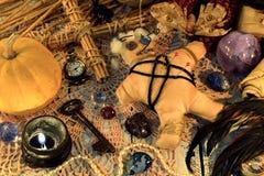 Poupée fantasmagorique de vaudou avec les goupilles, le potiron, la clé, la bougie noire et la croix sur la table de sorcière images libres de droits