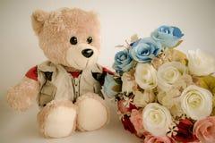 Poupée mignonne d'ours avec le bouquet rose Photographie stock