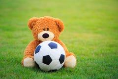 Poupée mignonne d'ours avec le football sur le champ de l'herbe Photos libres de droits