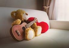 Poupée mignonne d'ours avec le grand coeur rouge sur le sofa blanc et l'espace vide Photographie stock