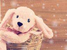 Poupée rose mignonne de chien dans le panier avec le fond en bois avec la couleur de filtre de vintage Images libres de droits