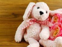 Poupée rose mignonne de chien et décoration rose artificielle de fleur sur le fond en bois Photographie stock