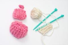 Poupée tricotée de chapeau avec la laine rose et aiguilles pour le tricotage Images libres de droits