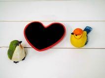 Poupées d'oiseau faites de stuc sur le fond blanc de chaise avec le petit coeur de conseil Images stock