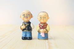 Poupées de grand-maman et de grand-papa dans le style uniforme chinois se tenant sur le fond en bois pendant la nouvelle année ch Photos stock