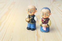 Poupées de grand-maman et de grand-papa dans le style uniforme chinois se tenant sur le fond en bois pendant la nouvelle année ch Photographie stock