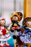 Poupées en bois habillées dans différents équipements poupées en bois faites main accrochant comme affichage Poupées décoratives Image libre de droits