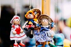 Poupées en bois habillées dans différents équipements poupées en bois faites main accrochant comme affichage Poupées décoratives Photos libres de droits