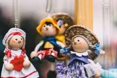 Poupées en bois habillées dans différents équipements poupées en bois faites main accrochant comme affichage Poupées décoratives Images libres de droits