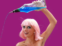 Pour. Beautiful female bartender pouring a blue liquid in a stream from a glass bottle.  Isolated on a purple background Royalty Free Stock Image