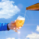 Pour beer into a glass against the sky. stock photo