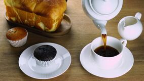 Pour black coffee into white ceramic coffee cup for breakfast.