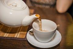 Pour tea from a teapot into a mug Royalty Free Stock Photos